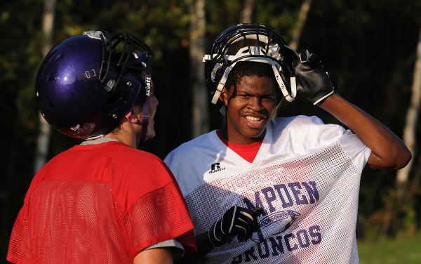 Isaiah Bess (right) talks with new teammate Matt Martin during Hampden Academy's first football practice of the season at Hampden Academy on Monday.