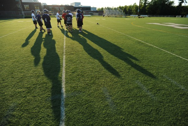 Shadows from returning and new recruits to Hampden Academy's football program extend across the field during the first practice at Hampden Academy on Monday.