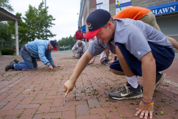 Jordan Clarke and members of the grounds crew clean bricks Thursday at Mansfield Stadium to get ready for the Senior League World Series in Bangor.