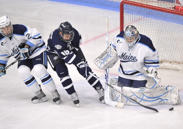 New Hampshire center Jeff Silengo slips between Maine defenseman Mike Cornell and goalie Martin Ouellette at Alfond Arena in Orono in 2010.