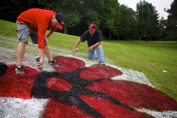 From left, Barrett Dionne and David Brookings paint a giant lobster on the field in back of Mansfield Stadium Thursday afternoon in preparation for the Senior League World Series in Bangor, which begins Sunday.