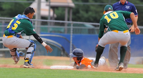 Europe-Africa's Manuel Piazza (center) slides safely into third base as Latin America's Luis F. Alonso (left) and Javier Garcia scramble for the ball. Piazza was nearly tagged while off second base, but was able get to third due to an error.