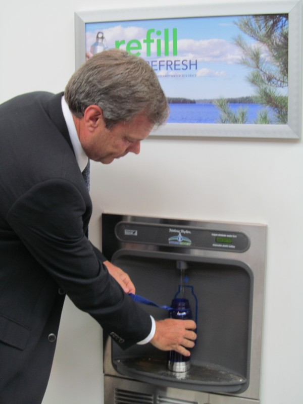Portland Water District board president Guy Cote adds his new water bottle to the more than 38,000 filled at this water bottle-filling station the district installed two years ago at Portland International Jetport.