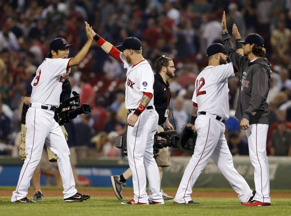 Boston Red Sox relief pitcher Koji Uehara (left) celebrates with his teammates after defeating the Baltimore Orioles 4-3 Wednesday night at Fenway Park.