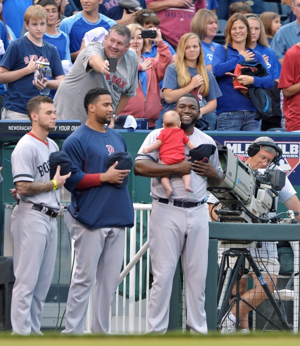 David Ortiz of the Boston Red Sox holds a young fan as a relative takes a photo from the stands during the playing of the national anthem before action against the Kansas City Royals at Kauffman Stadium in Kansas City, Missouri, on Thursday.