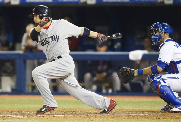 Boston's Shane Victorino hits a single that scores two runs as Toronto Blue Jays catcher J.P. Arencibia looks on in the 11th inning Tuesday night in Toronto. The Red Sox won 4-2.