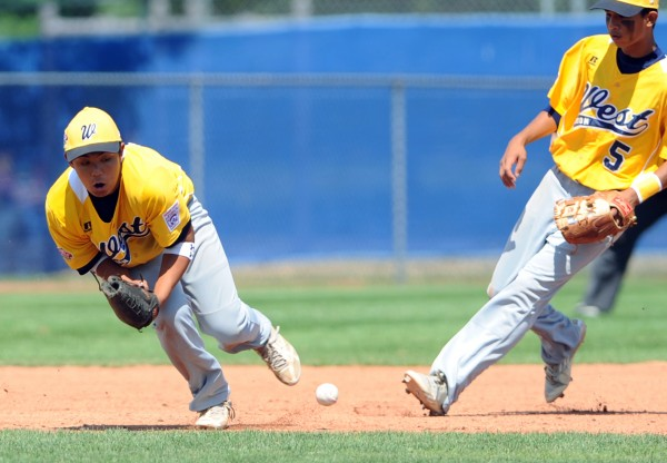 U.S. West third baseman Sanyo Lo misses the ball in the sixth inning Friday's semifinal game against U.S. East.  U.S. East won the game 9-4 and advances to the Senior League World Series championship game on Saturday at Mansfield Stadium in Bangor. At right is shortstop Kawaiola Takemura.