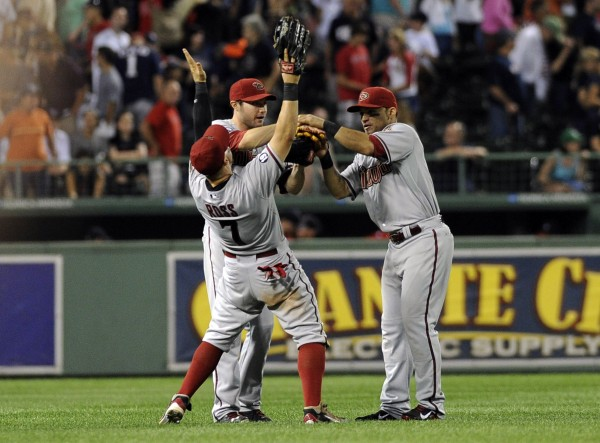 Arizona Diamondbacks right fielder Cody Ross (7), who played for the Boston Red Sox last season, celebrates defeating the Red Sox with his teammates at Fenway Park in Boston Friday night.
