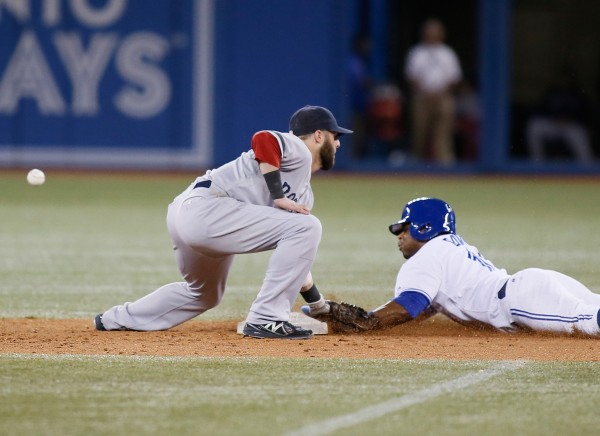 Toronto's Rajai Davis (11) slides into second base as the ball gets past Boston Red Sox second baseman Dustin Pedroia in the eighth inning at the Rogers Centre Thursday night. Toronto defeated Boston 2-1.