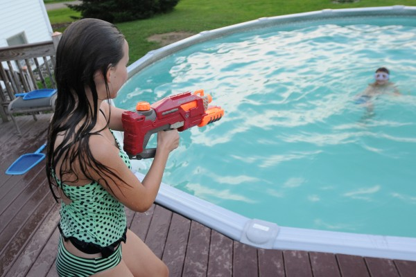 Olivia Johnson squirts her brother Nicolas during a water fight in the family's back yard pool during a pool party.