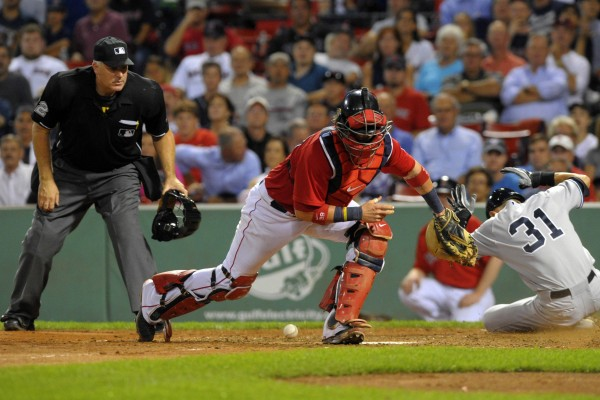 New York Yankees right fielder Ichiro Suzuki (31) slides safely past Boston Red Sox catcher Jarrod Saltalamacchia (39) during the ninth inning at Fenway Park in Boston Friday night.