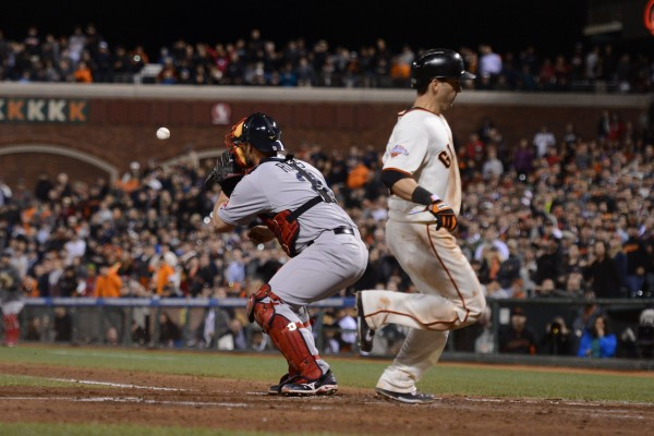 San Francisco's Marco Scutaro scores on a sacrifice fly by Buster Posey while Boston Red Sox catcher David Ross takes the late throw during the eighth inning at AT&T Park in San Francisco Tuesday night.