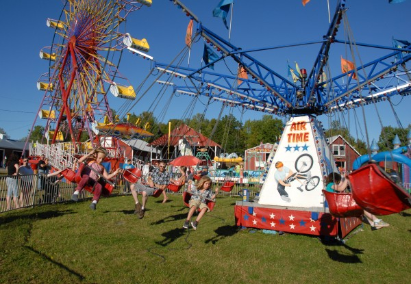 Riders swing outward in their seats as the Air Time ride spins against a busy backdrop at the 125th Annual Piscataquis Valley Fair in Dover-Foxcroft. The fair continues through Sunday.