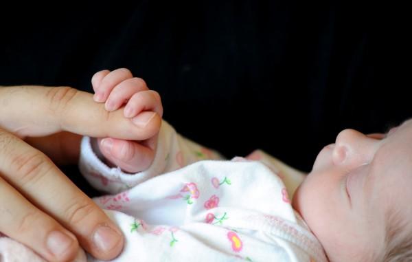 Two-week-old Ruby Ann Nichols grasps her father, Matt's, finger.