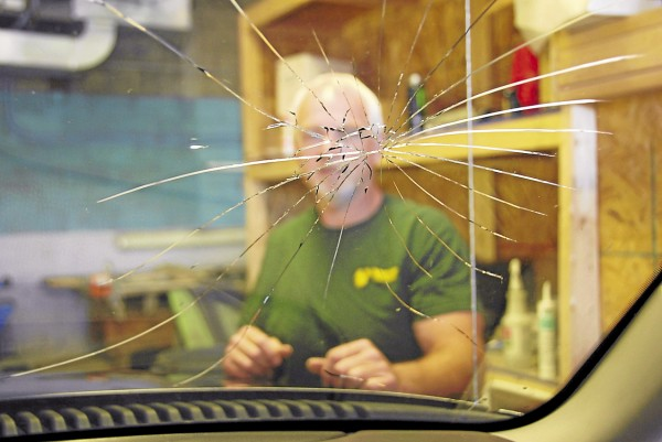 Bernie Lynch, who owns Viking Glass in Milford, examines a splintered windshield on Ford Explorer parked inside his company's service bay.