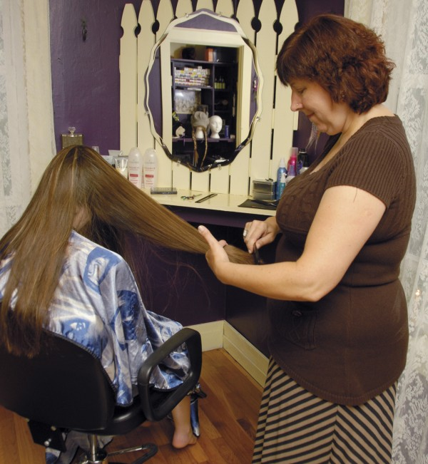 Licensed cosmetologist Paula Sides-Wilson brushes a customer's hair at the Beauty Cape salon, located at 69 Fifth St., Bangor. Sides-Wilson opened the salon in November 2012.
