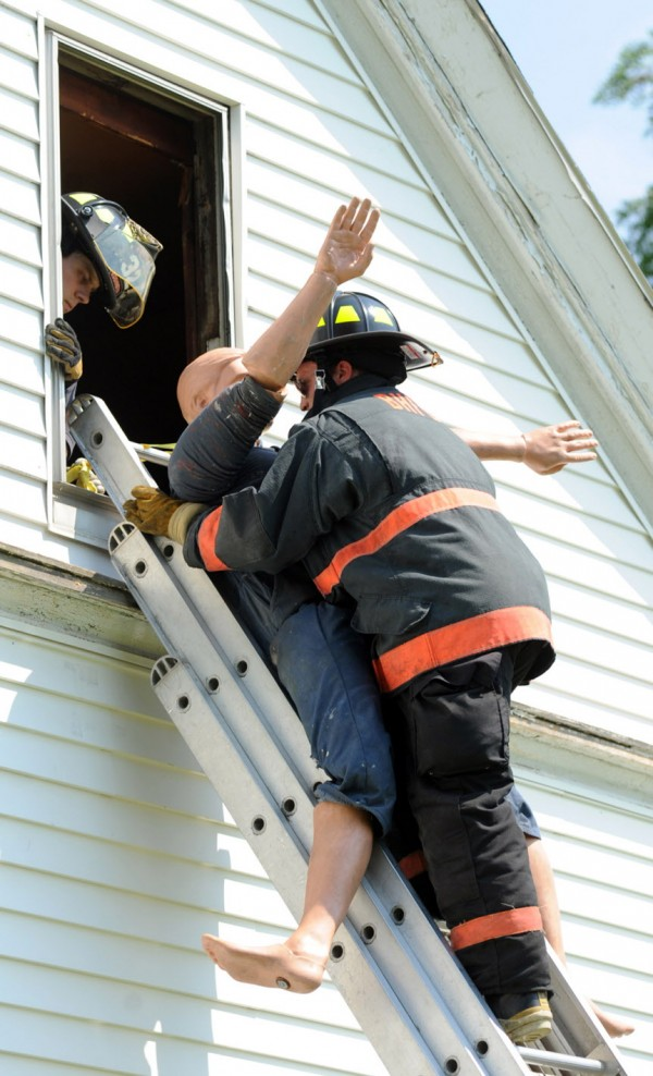 Jason Richter of the Bar Harbor Fire Department brings &quotRescue Randy,&quot a 215-pound mannequin, out a window and down a ladder during Penobscot County's Fire Academy on Thursday.  Twelve students practiced venting, search and rescue, and rescuing an unconscious victim out a window at a donated house in Orrington.