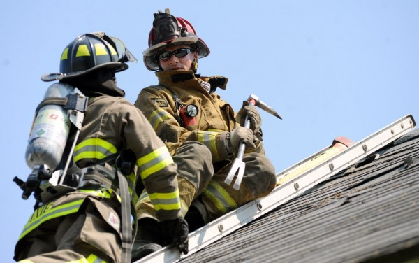 Instructor Chandler Corriveau helps firefighting student Christine Davis vent a roof on Thursday. Twelve students practiced venting, search and rescue, and rescuing a victim out a window at a donated house in Orrington.
