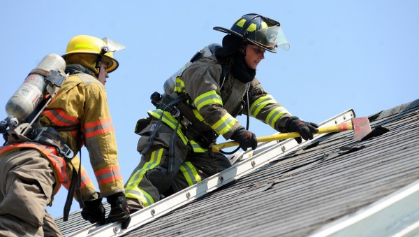 Christine Davis of the Glenburn Fire Department vents a roof on Thursday as part of Penobscot County's Fire Academy. At left is student Keith Nutter, Hermon Fire. Twelve students practiced venting, search and rescue, and rescuing a victim out a window at a donated house in Orrington.