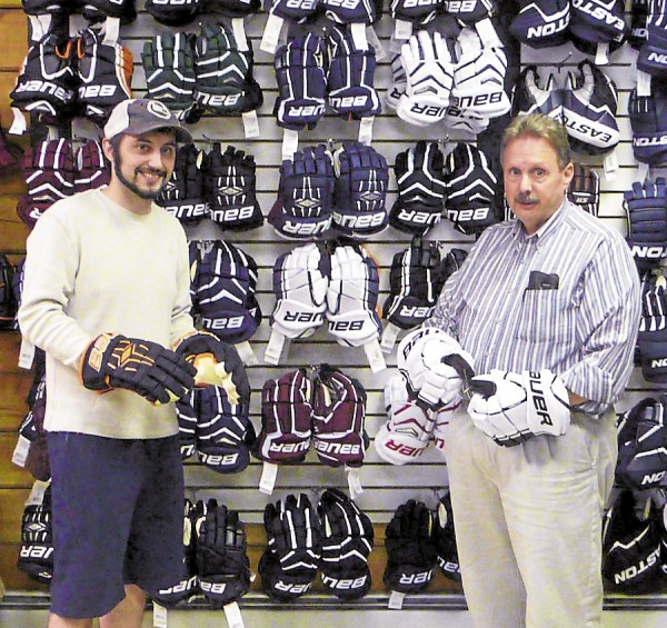 At Gunn's Sports Shop in Brewer, Manager Mike Merritt (left) and owner-president Rick Gunn display some hockey gloves sold at the skating-focused business.