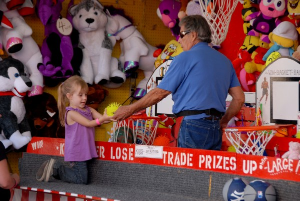 Her face betrays her excitement and pleasure as a little girl accepts the prize she won Saturday while participating in a midway basketball game at the 125th Annual Piscataquis Valley Fair in Dover-Foxcroft.
