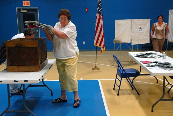 Bernadette Friel grabs a handful of ballots from the ballot box at the end of the Millinocket validation vote at Stearns High School on Tuesday, Aug. 20, 2013.