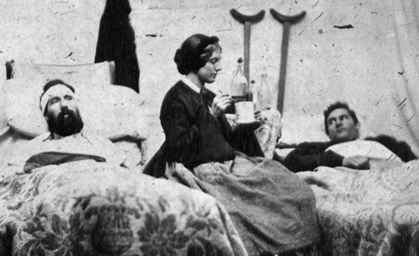 "Nurse Anne Bell cares for two wounded soldiers in a U.S. Army hospital in Nashville, Tenn. in late December 1864. These men were wounded during the two-day Battle of Nashville, an army-shattering defeat for the Confederacy. Evidence suggests that Bell, holding a large mug and probably a spoon, is feeding the young soldier on the right; he looks anxiously at her as she primly poses for the photographer. The crutches placed behind his bed suggest that this soldier was wounded in both legs. The older, bearded soldier on the left has suffered a head wound; his ""thousand-yard stare"" suggests that his attention has wandered elsewhere. Close examination of the photo also suggests that he may have lost an arm."
