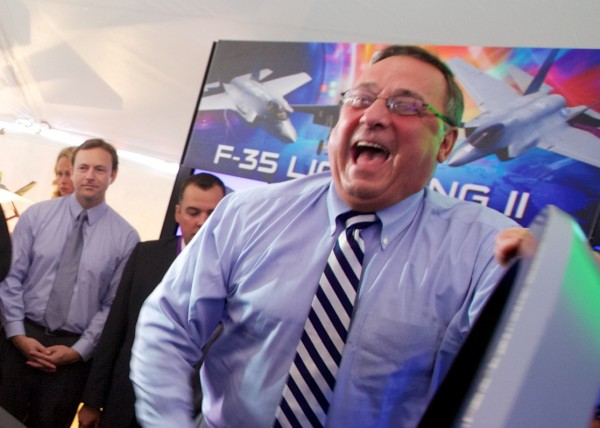 Governor Paul LePage laughs as Gary Hentz of Lockheed Martin gives him a set of plastic wings after the governor flew an F-35 Lightning II simulator at a Pratt & Whitney employee appreciation event in North Berwick on Friday morning.
