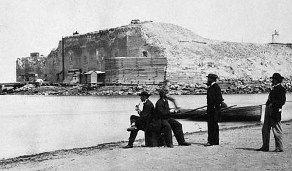 In March 1865 George Barnard photographed these civilians after they landed their rowboat on a sand bar adjacent to the battered Fort Sumter at Charleston, S.C. The camera angle is toward the northeast. Union troops had recaptured Fort Sumter a month earlier.