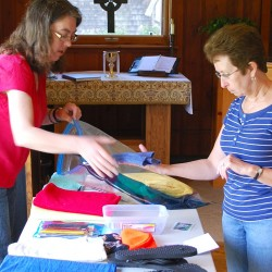 Mary Greene of Lubec and Helen Kilby of Edmunds, worshippers at Holy Trinity Chapel, assemble relief packages that will be sent to persecuted Christians living in the African nation of Sudan (Photo by Alan Andraeas).