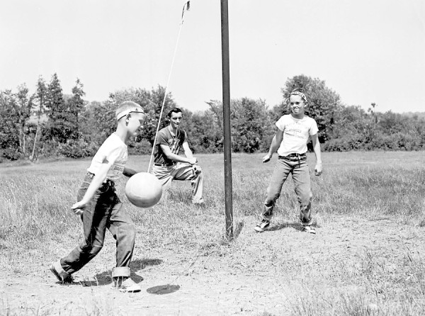 Participating in a tetherball game at Camp Prentiss in Hampden, Tim Furrow of Bangor (left) is just about to bang the ball back to Leigh White (right), also of Bangor, as athletic instructor Robert Kelley referees the game on Tuesday, July 10, 1956.