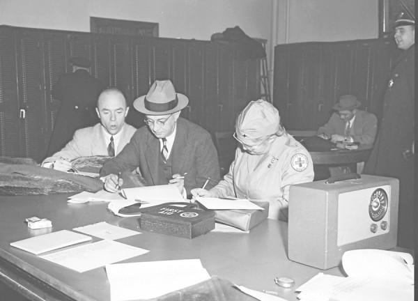 During a full-scale air-raid alert held in Bangor and Brewer on Tuesday, Dec. 18, 1951, (from left) Bangor Coty Manager Julian H. Orr, Civil Defense health director Henry J. Wheelwright, and Aubigne Smith of the Bangor Red Cross chapter check reports from the drill.