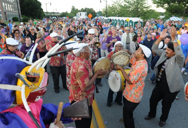American Folk Festival goers crowd the parade route as Jorge Arce and Raiz de Plena lead a mass of people to the Railroad stage as the the American Folk Festival gets under way on Friday along the Bangor Waterfront.