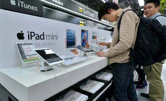 Customers check the Apple's tablet iPads at a Tokyo electric shop on May 31, 2013.