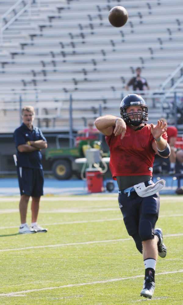 A UMaine football player makes a pass as head coach Jack Cosgrove watches during the Blue/White scrimmage on Tuesday at Morse Field on the UMaine campus in Orono.