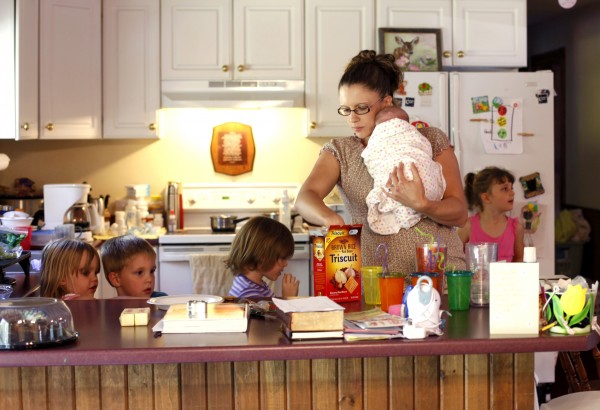 Crystal Stanley helps a few of her children fix a snack while balancing one of the two youngest twins in her spare arm.