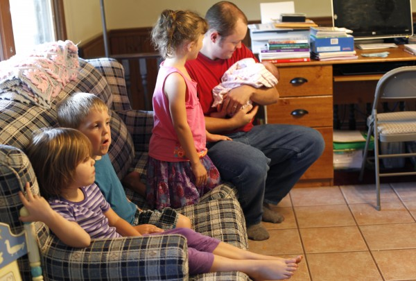 Joel Stanley sits with four of his seven children at the family's home in Lincoln, Maine.