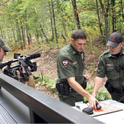 "Farmington District Warden Kris MacCabe, center, and his supervisor Sgt. Scott Thrasher shooting a scene for ""North Woods Law."" The second season of the Animal Planet reality show that follows wardens in the woods all over Maine starts Oct. 3."