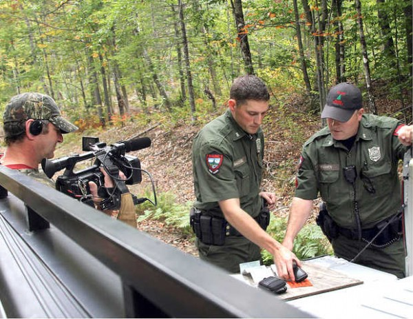Farmington District Warden Kris MacCabe, center, and his supervisor Sgt. Scott Thrasher shooting a scene for &quotNorth Woods Law.&quot The second season of the Animal Planet reality show that follows wardens in the woods all over Maine starts Oct. 3.