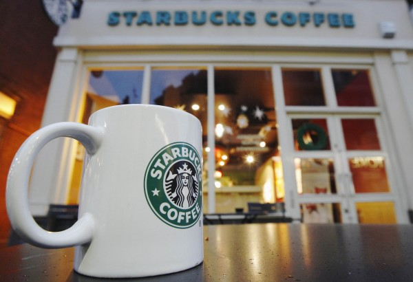 An empty cup is left on a table outside a Starbucks coffee shop in London December 1, 2011.