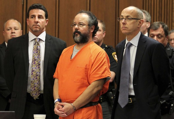 Ariel Castro (C), 53, stands between attorneys Craig Weintraub (L) and Jaye Schlachet as his sentence is read to him by judge Michael J. Russo in the courtroom in Cleveland, Ohio in this August 1, 2013 file photo. Castro, the Cleveland man sentenced to life in prison for the abduction, rape and torture of three women, was found dead in his Ohio jail cell, according to a prison official on September 3, 2013.