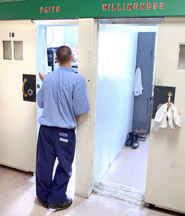 An inmate talks to another in the doorway of one of the numerous housing units at the Maine Correctional Center in Windham.