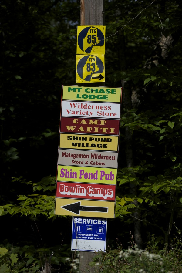 A camp and service sign shows several camps, snowmobiling trails and services near where Elliotsville Plantation Inc. has opened 40,000 acres to hunting and other recreational use.