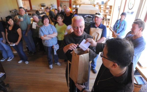 Franciscan Brothers Kenneth (center) and Stephen (right) pull names from a bag to decide who will get to buy the first ten bottles of beer that were made by the Friars' Brewhouse. The first bottles of the brew went up for sale at the Bangor Wine and Cheese Company Sunday.
