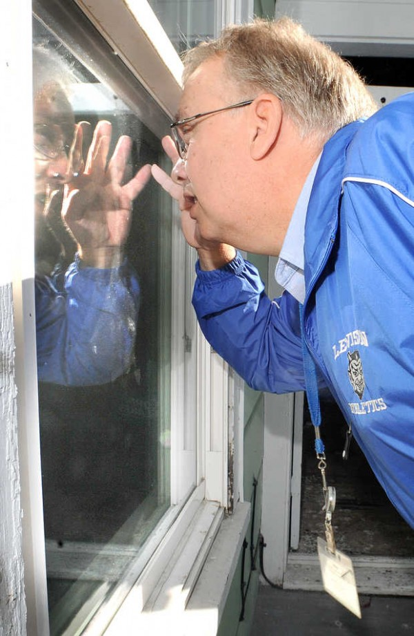 After knocking on the hallway door of a fourth-floor apartment on Walnut Street in Lewiston on Thursday morning, Lewiston Truant Officer Butch Pratt peeks through windows on the porch to see if anybody still lives at the address. The apartment was the address on file for a Lewiston High School freshman who had not been going to school.