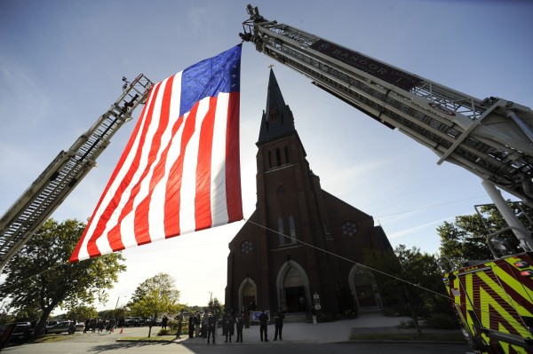With the help of its ladders, the Bangor Fire Department erected a huge U.S.flag in front of St. John Catholic Church in Bangor as part of Sunday's Blue Mass at the church on Sept. 20, 2009. The fourth annual Mass honored not only EMS, fire and law  enforcement personnel who died in the Sept. 11, 2001, terrorist attacks, but also those who serve today.
