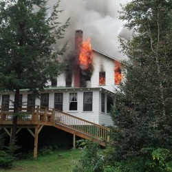 Flames shoot from Echo Lake Lodge and Cottages on Echo Lake in Fayette on Tuesday morning. The lodge, built in 1936 and owned by James and Evelyn Feagin, was destroyed.