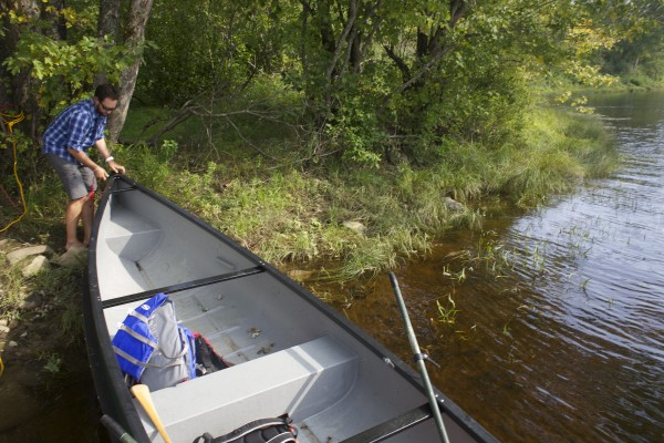 Lucas St. Clair launches a square stern canoe onto the East Branch of the Penobscot River into an area where Elliotsville Plantation Inc. has opened 40,000 acres to hunting and other recreational use.