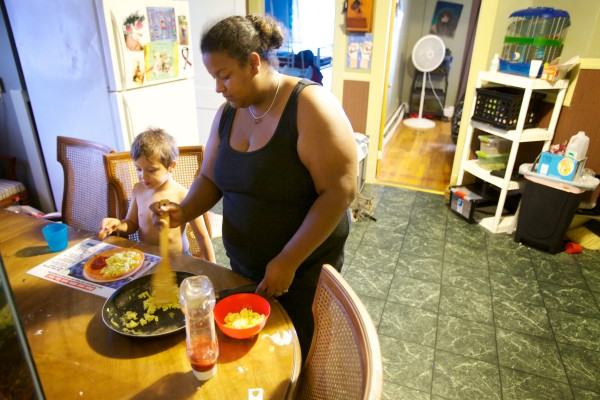 Samarali &quot€œSam&quot€ Daniels, 23, makes breakfast for her son Hector, 5, in their Augusta apartment. Their family is among 25,000 Mainers teetering on the edge and now in jeopardy of losing access to affordable health care.