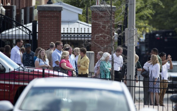 Military and civilian employees leave after a shooting at the Washington Navy Yard in Washington September 16, 2013.